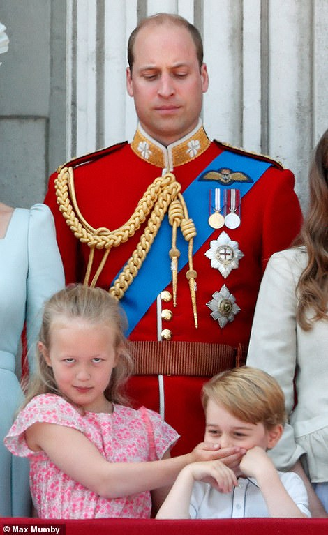 Prince William looks on as Savannah Phillips (bottom-left) puts her hand over Prince George during the trooping of the colour in June