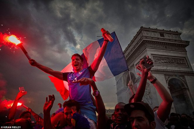 People are pictured celebrating in the streets of Paris after France won the FIFA World Cup in July last year. They are pictured near the French capital's Arc de Triomphe