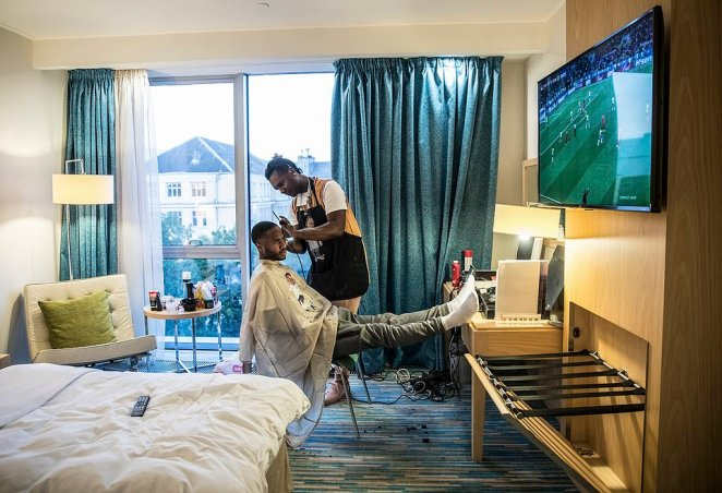 Raheem Stirling is pictured getting his hair cut in his hotel room before England's World Cup match in Kaliningrad, Russia. Stirling is seen watching a football match on TV as the barber cuts his hair