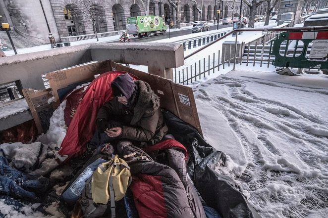 A homeless man is pictured sleeping out on the streets of London in temperatures of -3C, just half a mile away from the British House of Commons