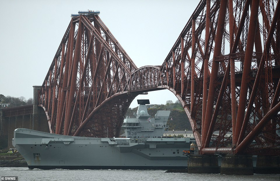 HMS Queen Elizabeth goes under the Forth Rail Bridge, and Queens Ferry Crossing in Scotland as it returns to the docks for scheduled maintenance last month