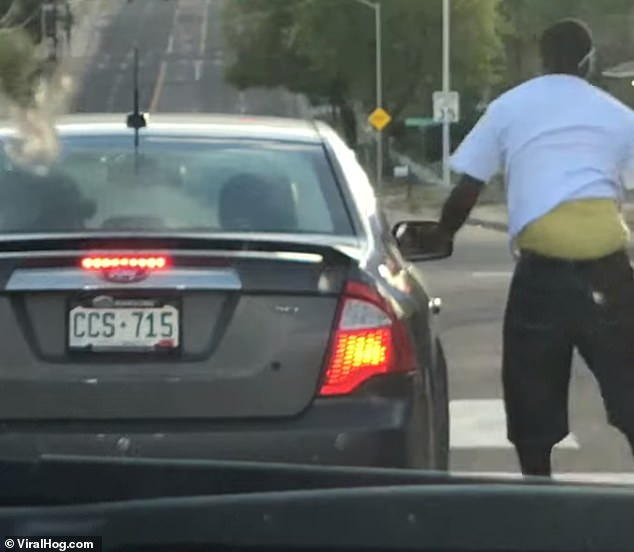 The car eventually comes to a stop at traffic lights and the man gets down and walks away