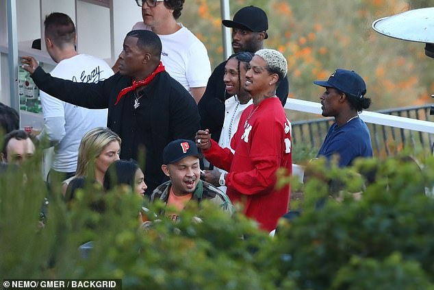 Relaxed: He chatted to music executive Alexander, who was pictured wearing a red jumper
