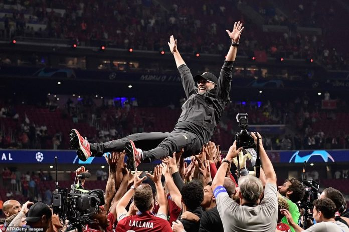 The Liverpool squad hoist their manager Jurgen Klopp above their heads and throw him in the air after he guided them to the coveted title