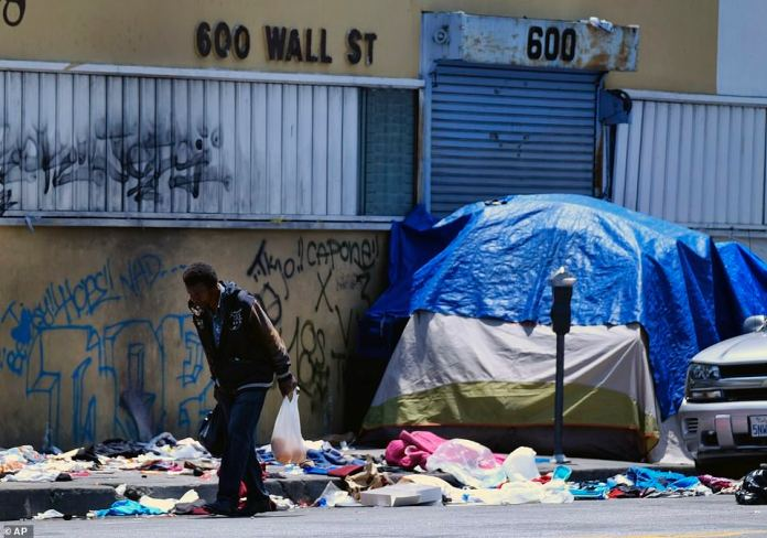 The police union says that homeless camps need to be cleaned up following recent diagnosis and other cases of hepatitis A virus and staph infection. A homeless man is photographed walking down a street lined with rubbish in front of the Los Angeles Police Station in downtown Los Angeles.