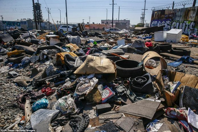 Heaps of garbage remain near the intersection of 25th St. and Long Beach Ave. Downtown images show a build-up of garbage as workers struggle to get their neighborhood clean. They are photographed wearing facial masks among dirt and grime