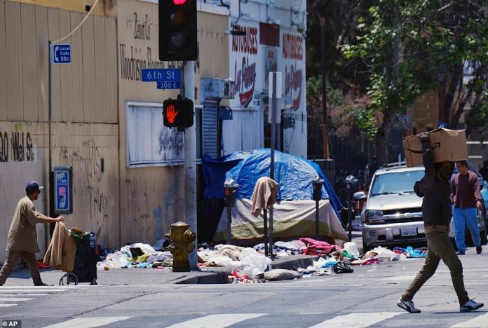 The union representing the LAPD is demanding a clean-up of the homeless camps in the city after a detective working in the city center is diagnosed with typhoid fever and two others have similar symptoms. Pedestrians cross street litter near Los Angeles police station in downtown Los Angeles on Thursday