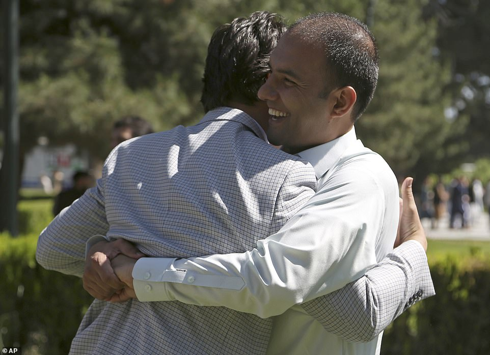 Men hug each other after offering Eid al-Fitr prayers at the presidential palace in Kabul, Afghanistan