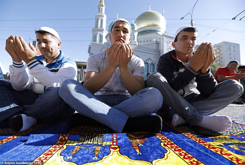 Worshippers offer up prayers in the early-morning light outside the Moscow Cathedral Mosque in Russia, on Tuesday