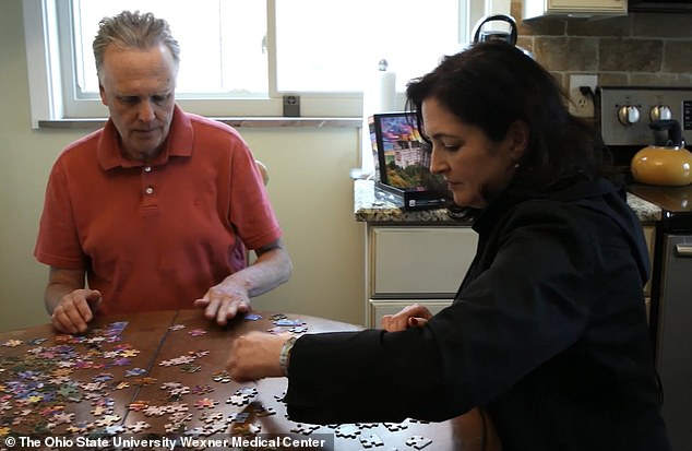 David Shorr, of Bexley, Ohio, was diagnosed with Alzheimer's disease at age 56. Pictured: Shorr, left, completing a jigsaw puzzle with his wife, Kim
