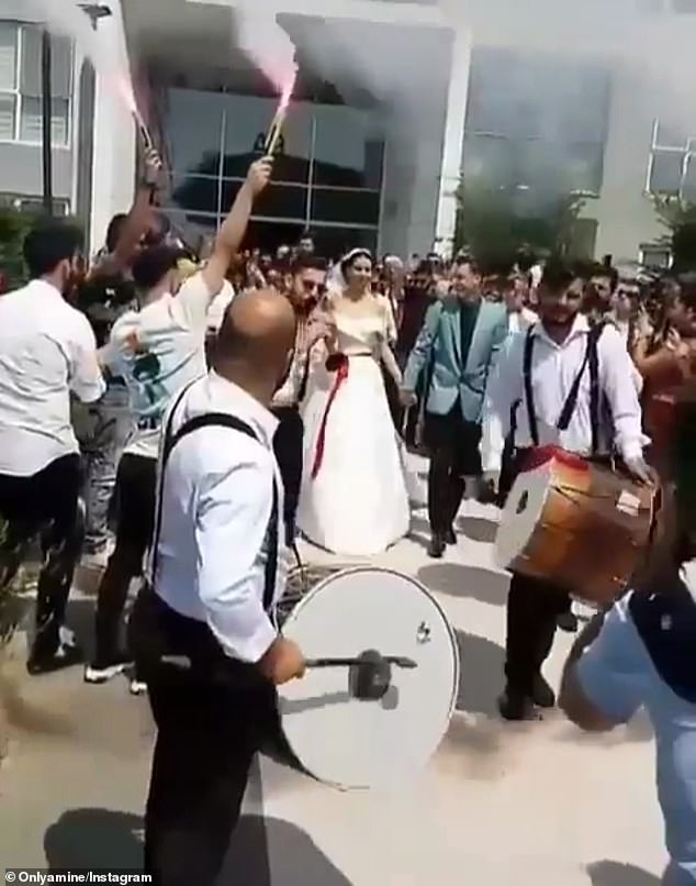 Ozil was seen walking with his new wife alongside a parade of beating drums and flares