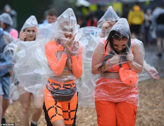 Festival-goers wear their waterproof as they wade through the mud at Heaton Park in Manchester.The event comes as the Met Office issues four severe weather warnings for rain