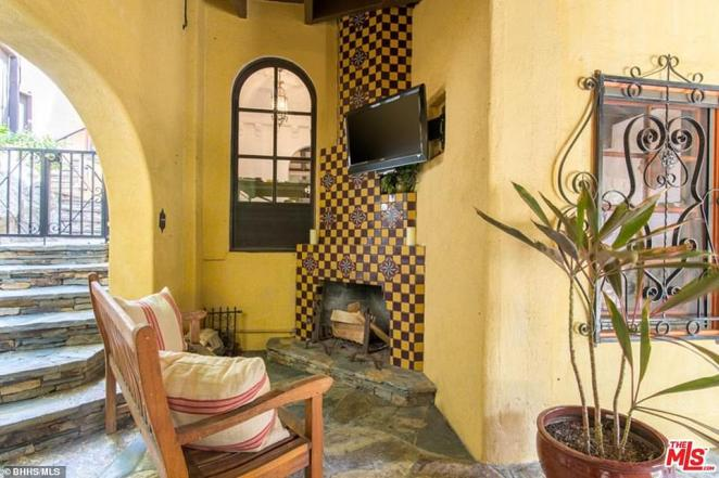 Cozy: This little spot is covered by a roof but backs on to a staircase leading outside. In this image, a bench with two cushions has been placed in front of a TV screen, with a fireplace decorated in a similar yellow color to the rest of the walls