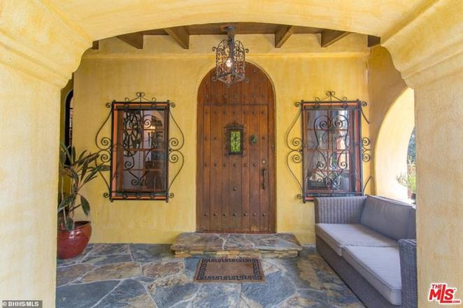 Entrance: This view shows the Mediterranean inspiration of the property with colors typical of sunlit buildings in southern Europe, as well as ornate decoration on the windows and a large wooden door
