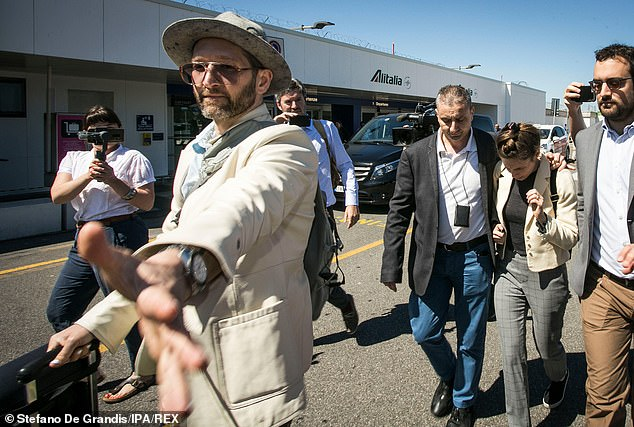 36-year-old novelist Christopher Robinson, who is engaged to Knox (back right), extended his arm towards the passing cameras as the couple touched down at the airport