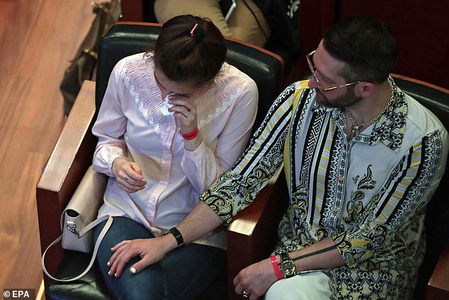 The former US murder suspect (left) wipes his eyes at the Italian event on Friday, comforted by her boyfriend Christopher Robinson