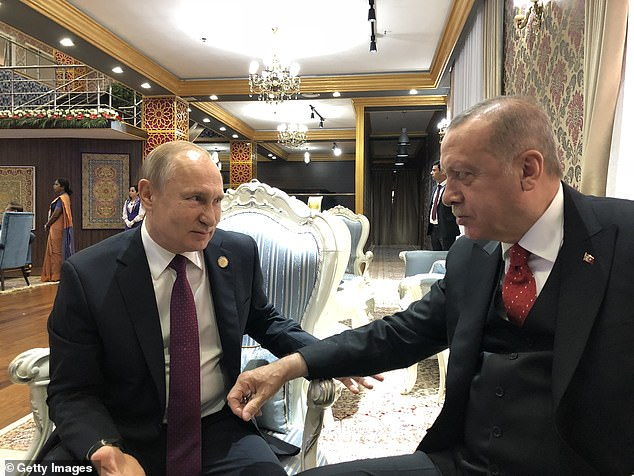 Turkish President Recep Tayyip Erdogan (right) meets with Putin at an informal meeting during the conference