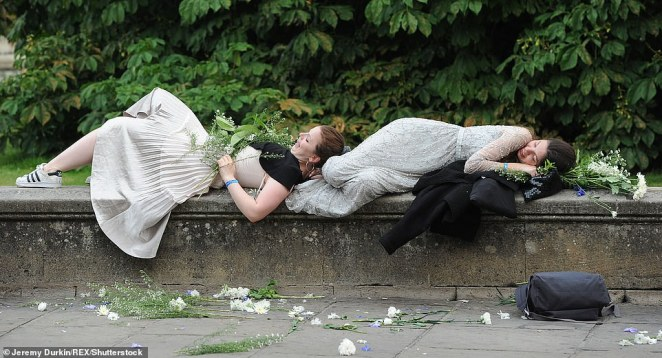 Two students need a lie down on a wall after the 2017 Trinity May Ball and made sure to hold on to their flowers