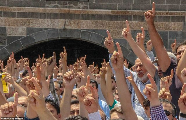 Men hold up their index finger indicating 'Oneness of God' during symbolic funeral prayers in Turkey for Mohamed Morsi the day after the former Egyptian president died in Cairo