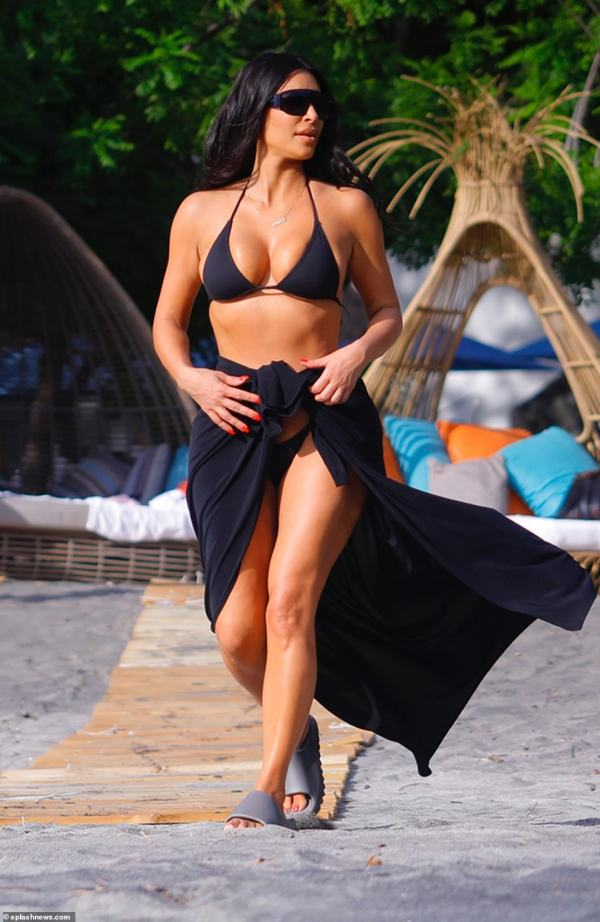 Beach babe! Kim Kardashian couldn't keep her killer figure under wraps for too long as she stepped out on to the beach in a tiny black bikini