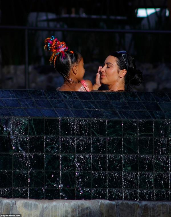 Water babies: North washed off her mom's face while playing in the jacuzzi
