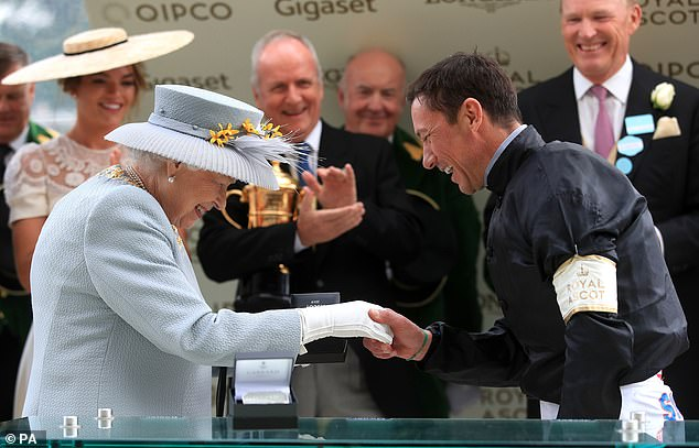 The Queen presents the trophy to Frankie Dettori after winning the Gold Cup on Stradivarius
