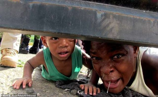 A woman (right) from Haiti cries for assistance for her sick son, 5, while her one-year-old child (left) crawls on the ground during an uprising by African and Haitian migrants at the shelter