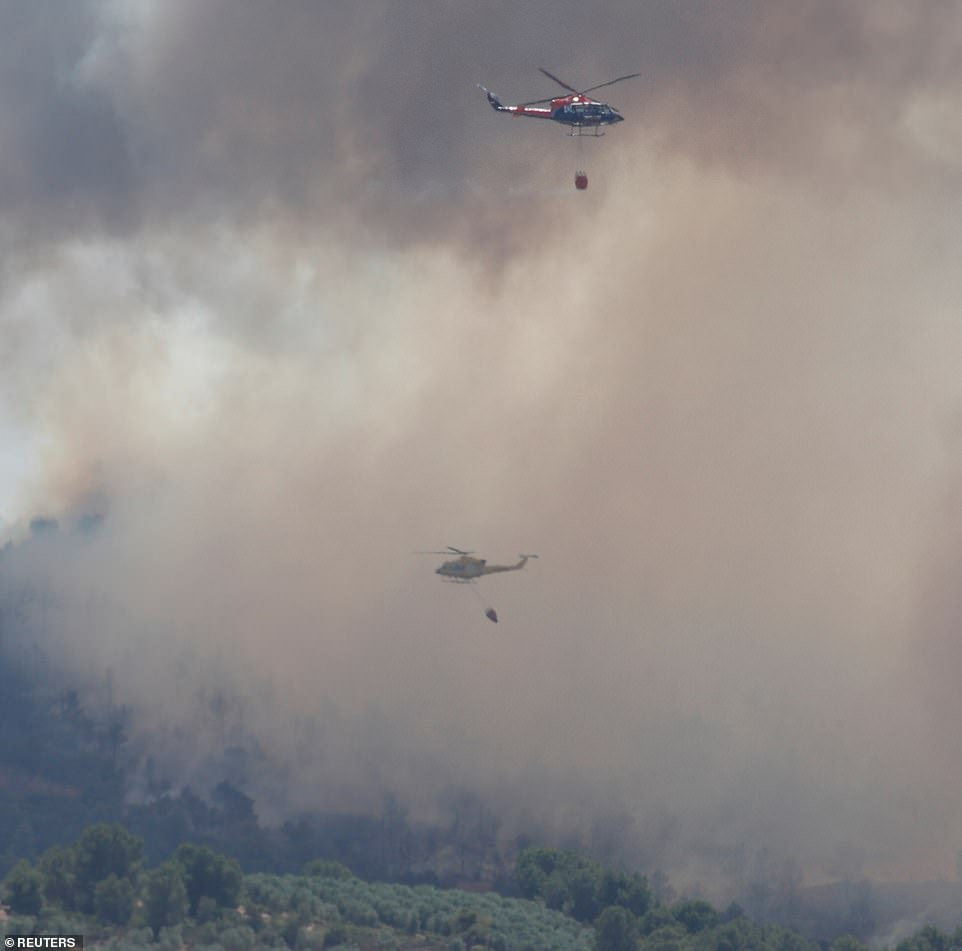 Helicopters drop water over a fire during a forest fire near Bovera, west of Tarragona, Spain. Officials said yesterday the blaze, fanned by hot winds, was 'out of control'