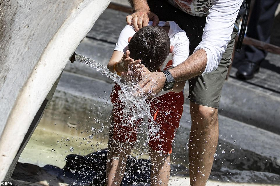 The new record makes France just the seventh European country to have recorded a plus 113F (45C) temperature, along with Bulgaria, Portugal, Italy, Spain, Greece and North Macedonia. Pictured:Tourists cool themselves off in the 'Barcaccia' fountain at Spain square in Rome, Italy