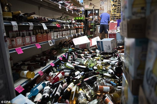 A man walks in the middle of fallen and broken bottles in a gas station and liquor store the 178 after an earthquake in Ridgecrest