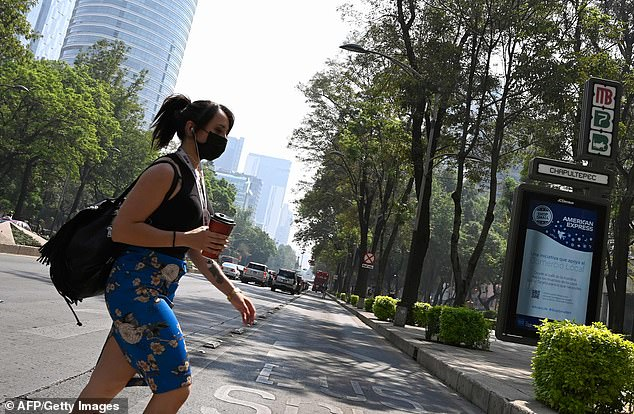 The subjects of the study had to do with their chests. Pictured: A woman wearing a face mask against dangerously high levels of pollution in a city