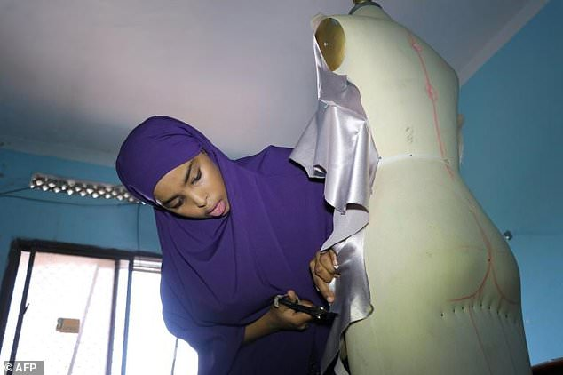 Muna Mohamed Abdulahi, owner of Mkena Designs, cuts some fabric on a mannequin in her shop