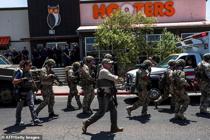 Law enforcement officials are seen in front of a Hooters restaurant, which was placed on lock down during the shooting