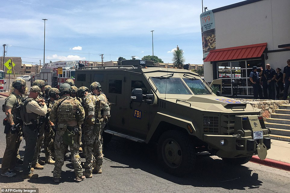 Heavily armed police are seen next to an FBI armored vehicle next to the Cielo Vista Mall in El Paso on Saturday