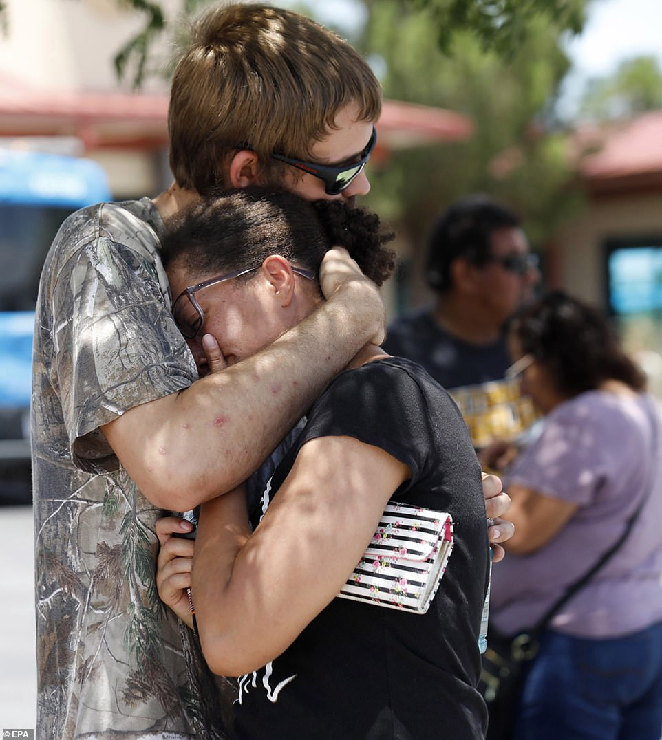 Kendall Long (left) comforts Kianna Long (right) who was in the freezer section of a Walmart during the shooting