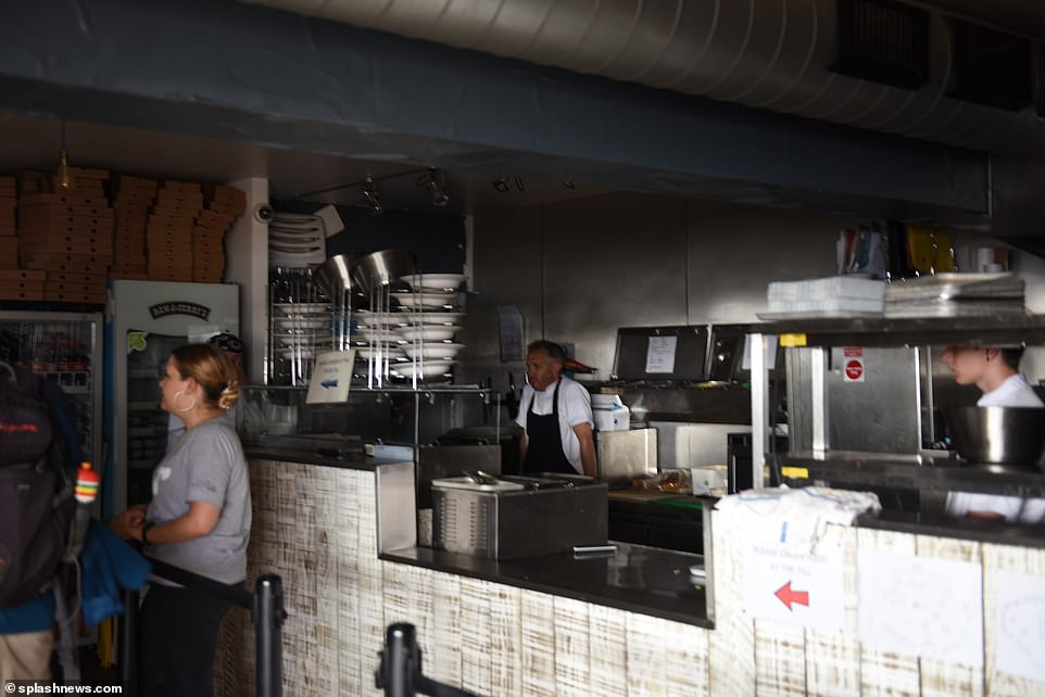A chef in Cornwall stands in the dark as machines and lights were switched off during the mass outage yesterday. It has impacted the Fistral Beach Boardmasters surf competition
