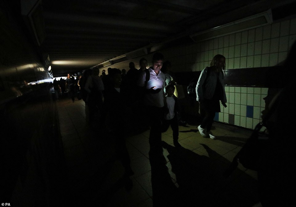 Commuters had to use the torches on their phones as they walked in complete darkness at Clapham Junction during a power cut