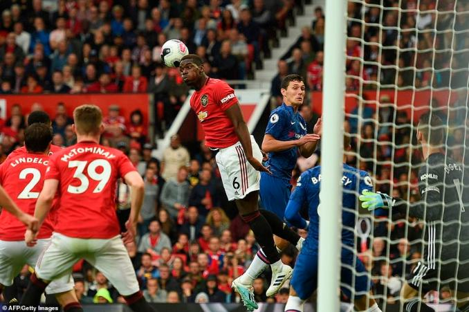 Paul Pogba leaps in the air to head the ball clear and remove the danger from Manchester United's penalty box