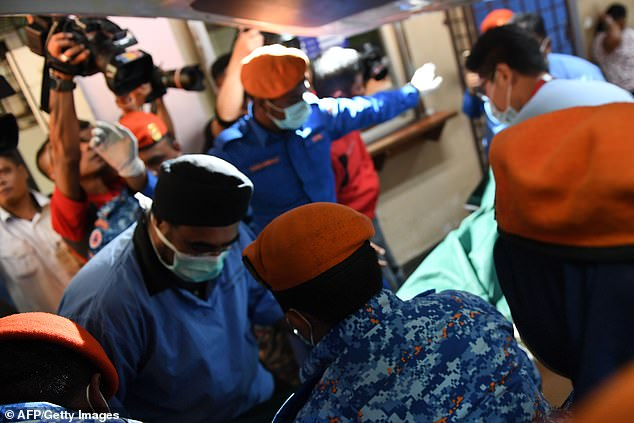 Rescue workers carry Noar's body as it arrives at Seremban hospital, after she was found dead near a stream in the jungle surrounding the eco-resort