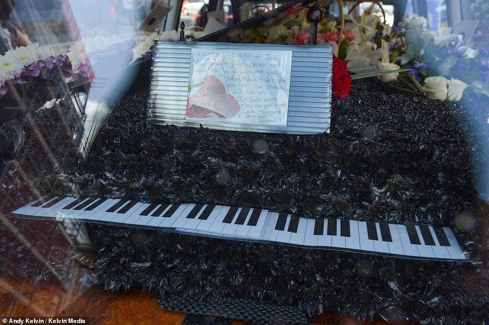 A floral display resembling a piano is left in the window of the hearse after Joe Longthorne's coffin was carried into the church