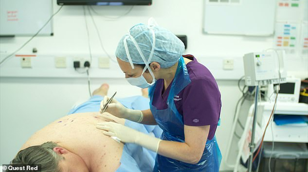 Dr Emma sets to work and pops an impressive 17 cysts and blackheads from Scott's back - much to his relief. Pictured during the procedure