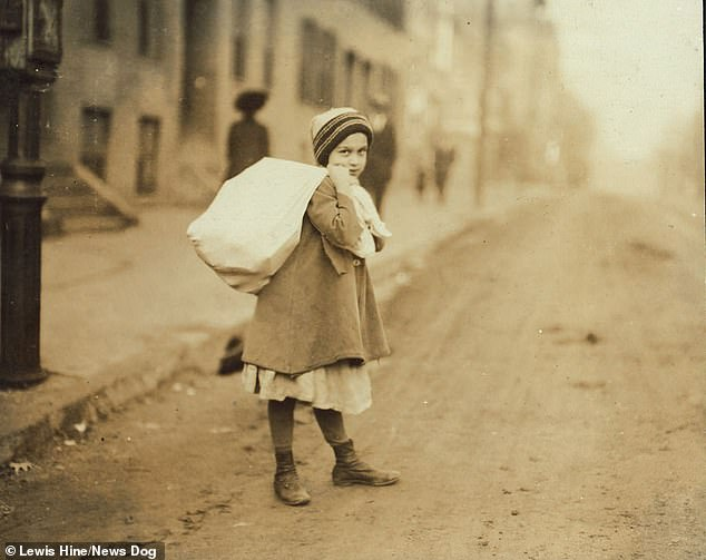 An eight-year-old girl in Worcester, Massachusetts,  stops to look at the camera as she carries a huge sack of goods on her back. She is seen struggling to lift it up the hill as she desperately tries to finish her job in the early morning so she can go to school