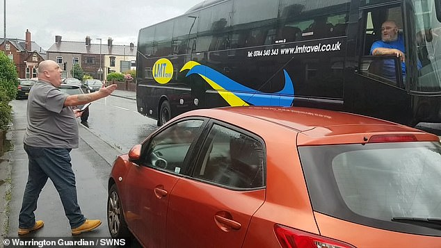 Pictured: The bald man rages at a coach driver after leaving his car to scream abuse at the man
