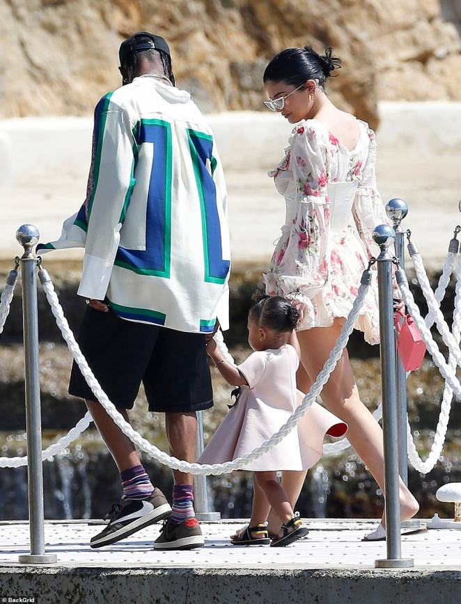 Meanwhile: Make-up mogul Kylie looked absolutely incredible in a into a corseted floral mini-dress and a pair of kooky glasses as she and Travis swung little Stormi, 18 months, up in the air as they joined the rest of the group on a boat