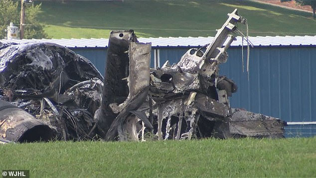 The charred remains of the plane are seen above on the grassy field at the Tennessee airport