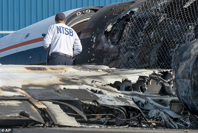 ANational Transportation Safety Board investigator is seen surveying the charred plane