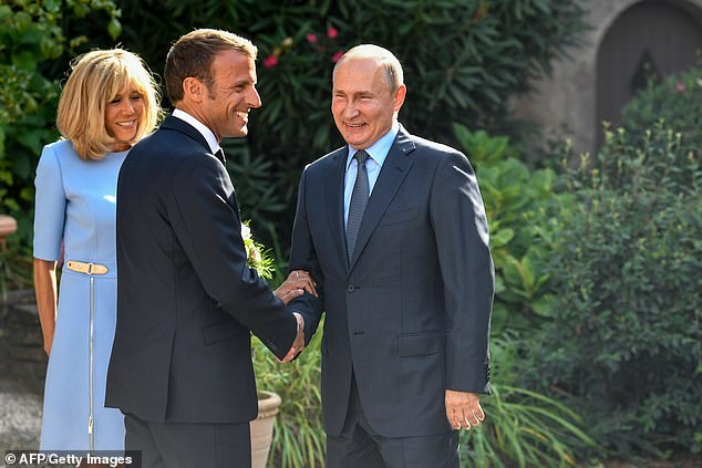 French President Emmanuel Macron (C) and his wife Brigitte Macron (L) welcome Russia's President Vladimir Putin, at the French President' summer retreat of the Bregancon fortress on the Mediterranean coast, near the village of Bormes-les-Mimosas, southern France