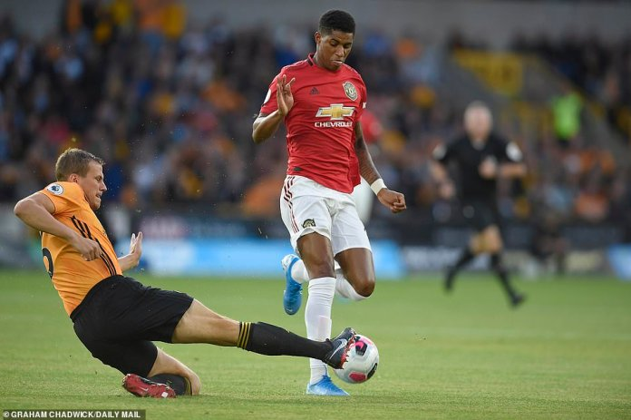 England star Rashford is tackled by Wolves centre-back Ryan Bennett during the opening stages on Monday night
