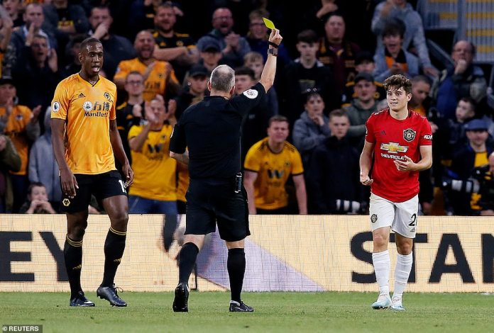 United new boy Daniel James, handed his first start for the club, is shown a yellow card for diving by referee Jon Moss