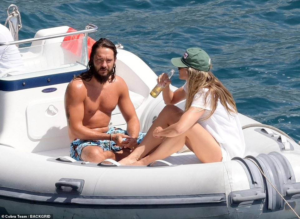 Swoon: Heidi appeared besotted with her man as he glistened with water while drying off on the boat